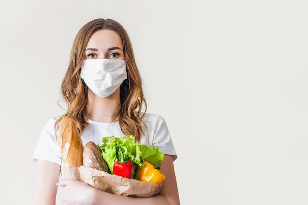 Jovem mulher com máscara médica detém um saco de papel com alimentos, frutas e legumes, pimenta, baguete, alface sobre fundo cinza, entrega em domicílio, coronovírus, quarentena, ficar em casa conceito, cópia espaço