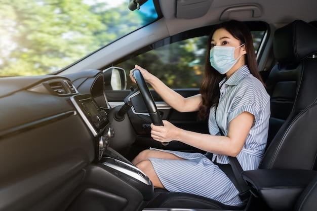 Jovem mulher com máscara médica, dirigindo um carro. para proteger a pandemia de covid-19 (coronavírus)