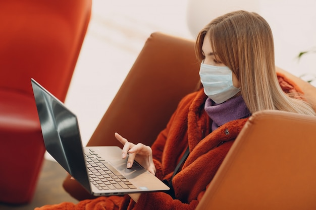 Jovem mulher com máscara médica e laptop em uma cadeira
