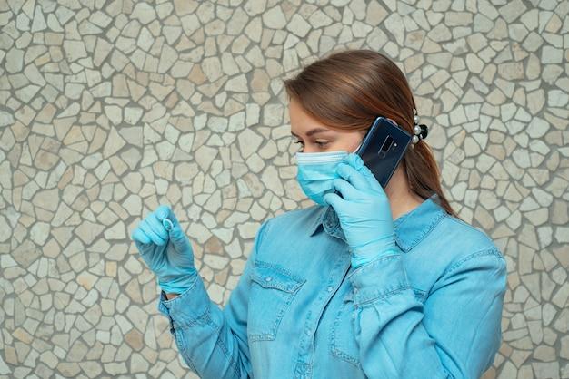 Jovem mulher com máscara médica olhando termômetro