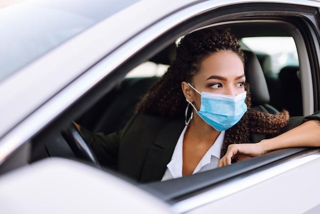 Jovem mulher com máscara médica protetora, dirigindo um carro.