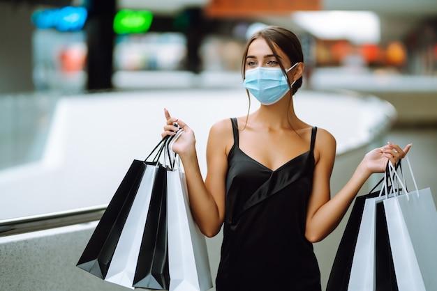 Jovem mulher com máscara médica protetora estéril no rosto com sacolas de compras no shopping.
