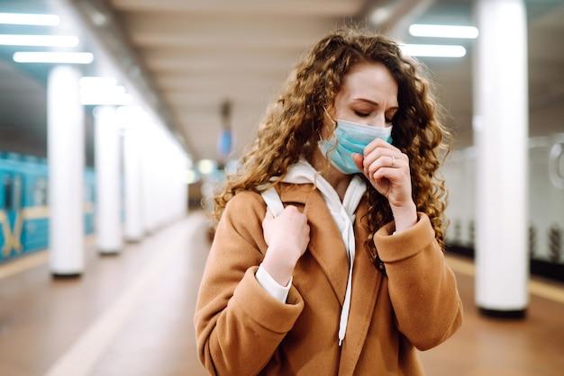 Jovem mulher com máscara médica protetora estéril tossindo na estação de metrô.