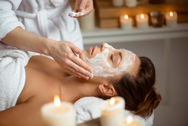 Jovem mulher com máscara para rosto relaxante no salão spa.