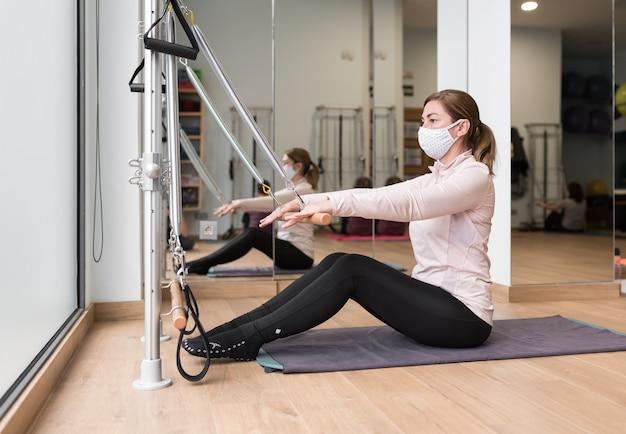 Jovem mulher com máscara praticando pilates em um estúdio. ela está sentada em um tapete e usa uma máquina