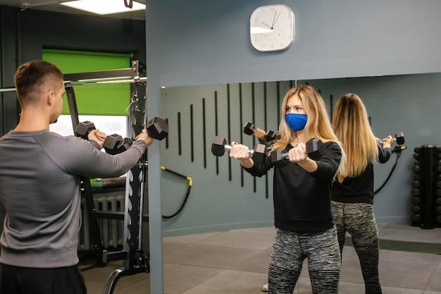 Jovem mulher com máscara protetora malhando com o personal trainer na academia durante a pandemia de covid-19. ela está bombeando seus músculos com halteres. foco suave