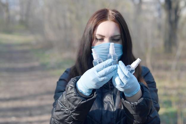 Jovem mulher com máscara protetora mostra frascos de spray desinfetante ao ar livre em madeira de primavera