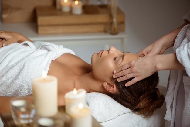 Jovem mulher com massagem de rosto relaxante no salão spa.