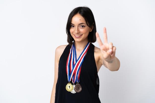 Jovem mulher com medalhas isoladas em um fundo branco sorrindo e mostrando sinal de vitória
