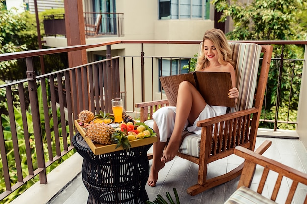 Jovem mulher com menu nas mãos dela, sentado no restaurante ao ar livre em verdes e sorrindo. tabela de frutas e suco tropical diferente
