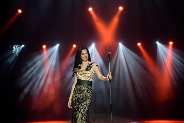 Jovem mulher com microfone na mão em evento de entretenimento.