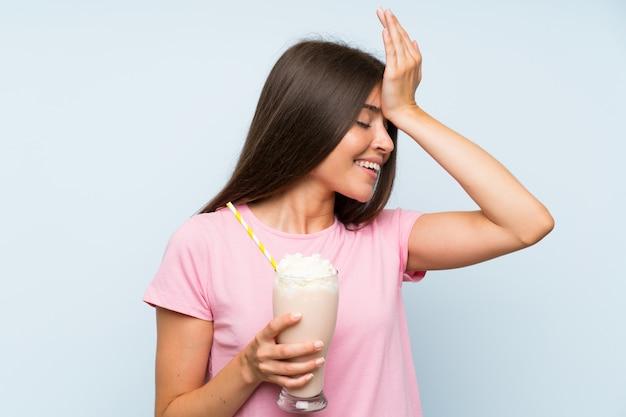 Jovem mulher com milk-shake de morango sobre parede azul isolada percebeu algo e pretendia a solução