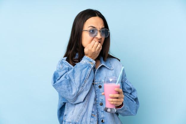 Jovem mulher com milk-shake de morango sobre parede azul, nervoso e assustado, colocando as mãos na boca