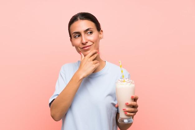 Jovem mulher com milk-shake de morango sobre parede rosa isolada, pensando uma idéia