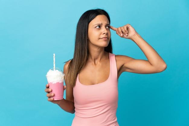 Jovem mulher com milkshake de morango tendo dúvidas e pensando