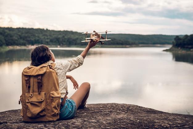 Jovem mulher com mochila e avião modelo à beira do lago