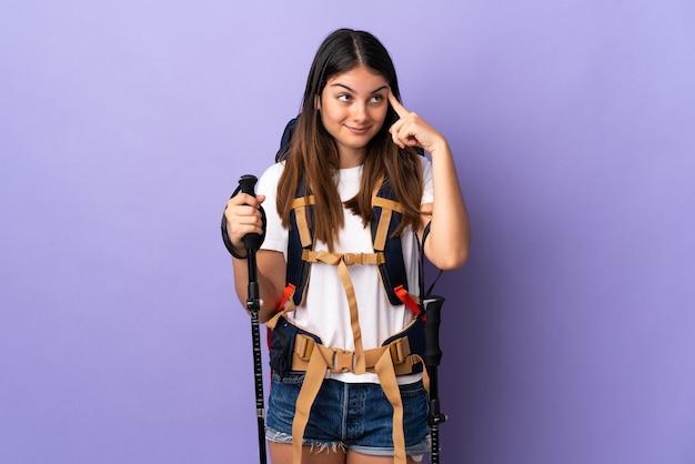 Jovem mulher com mochila e bastões de trekking isolados na roxa, tendo dúvidas e pensando