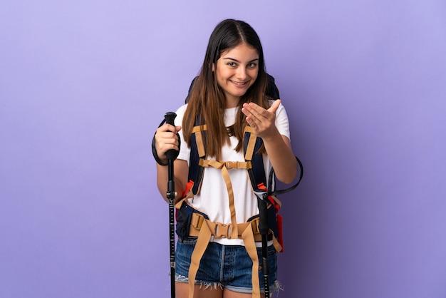 Jovem mulher com mochila e bastões de trekking isolados no roxo, convidando para vir com a mão. feliz que você veio