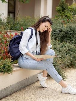 Jovem mulher com mochila e mapa