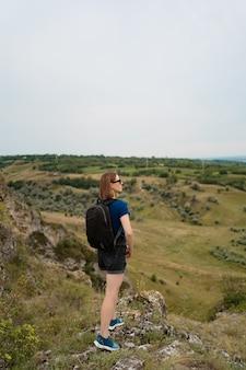 Jovem mulher com mochila em pé na beira do penhasco e olhando para o céu e a bela natureza.