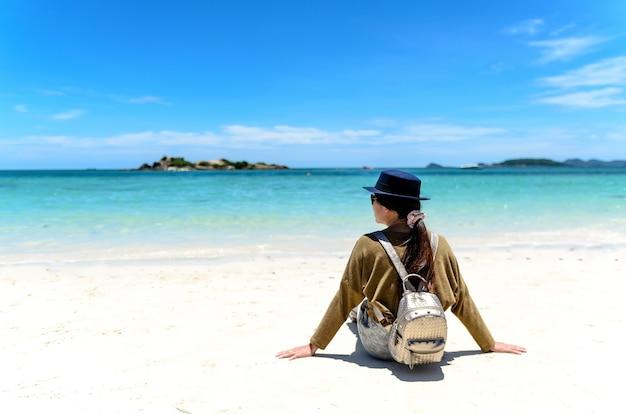 Jovem mulher com mochila sentado na praia solitária e olhando para o mar.
