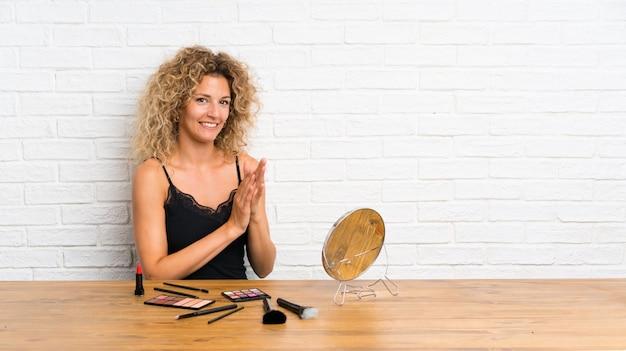 Jovem mulher com muita escova de maquiagem em uma mesa aplaudindo
