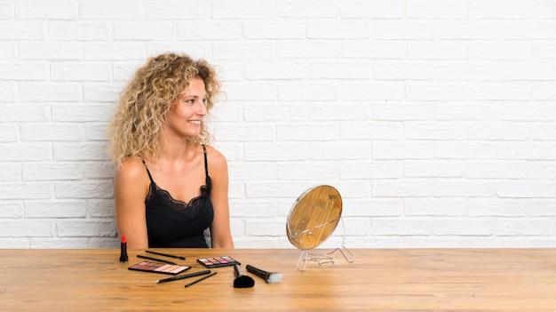 Jovem mulher com muita escova de maquiagem em uma mesa, olhando para o lado