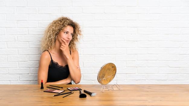 Jovem mulher com muita escova de maquiagem em uma mesa pensando uma idéia