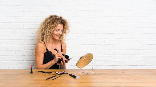 Jovem mulher com muita escova de maquiagem em uma tabela