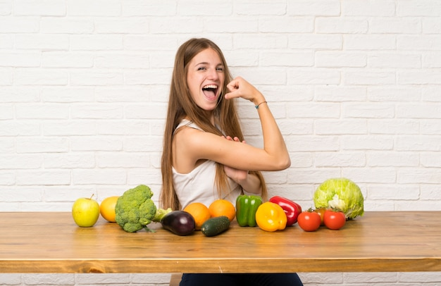 Jovem mulher com muitos legumes fazendo gesto forte