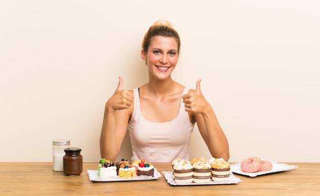 Jovem mulher com muitos mini bolos diferentes em uma mesa dando um polegar para cima gesto