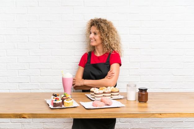 Jovem mulher com muitos mini bolos diferentes em uma mesa, olhando para o lado