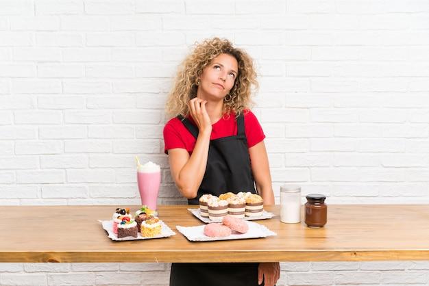 Jovem mulher com muitos mini bolos diferentes em uma mesa pensando uma idéia