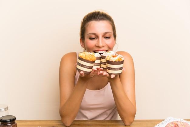 Jovem mulher com muitos mini bolos diferentes em uma tabela