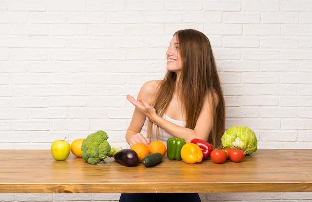 Jovem mulher com muitos vegetais, estendendo as mãos para o lado para convidar para vir