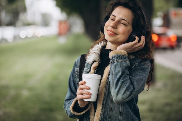 Jovem mulher com música e bebendo café