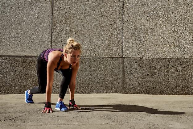 Jovem mulher com o corpo do ajuste que salta e que corre contra o fundo cinzento.