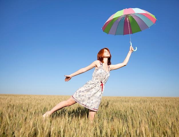 Jovem mulher com o guarda-chuva no campo de trigo nas horas de verão.