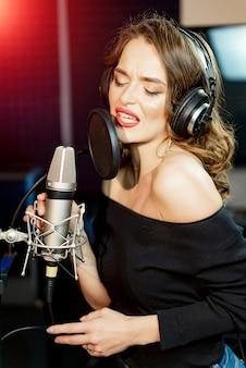 Jovem mulher com o microfone profissional no estúdio de gravação.