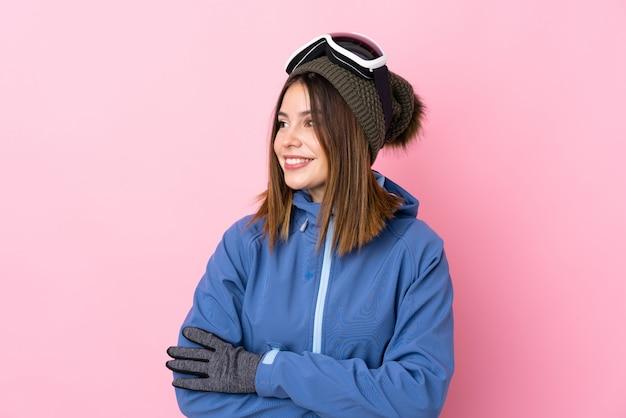 Jovem mulher com óculos de esqui na parede rosa