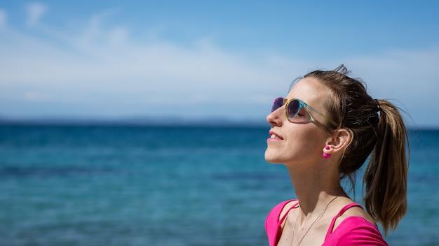 Jovem mulher com óculos de sol coloridos, em pé à beira-mar, aproveitando o dia ensolarado.