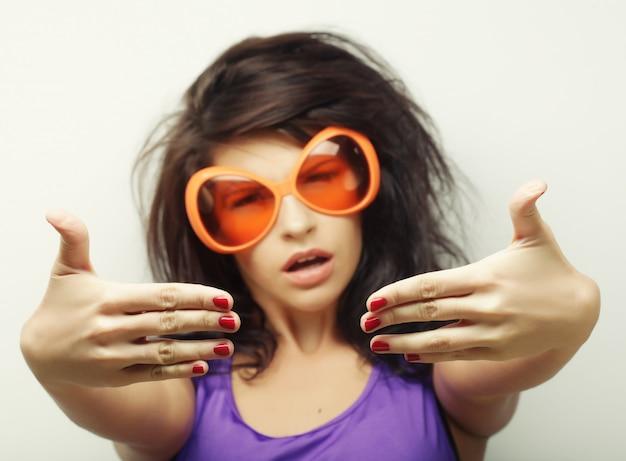 Jovem mulher com óculos de sol grandes laranja