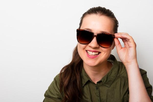 Jovem mulher com óculos de sol sorrindo