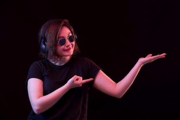 Jovem mulher com óculos escuros e camiseta preta segurando algo