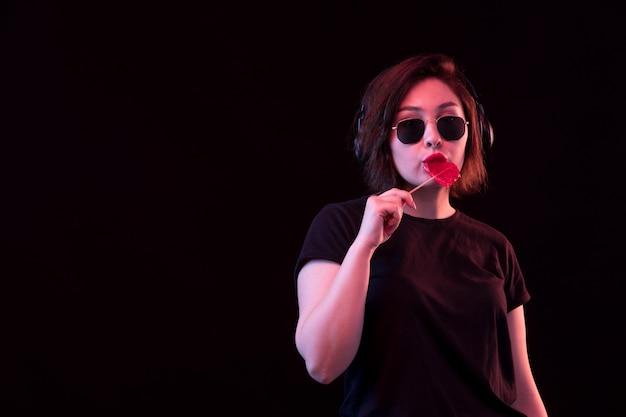Jovem mulher com óculos escuros e camiseta preta usando fones de ouvido