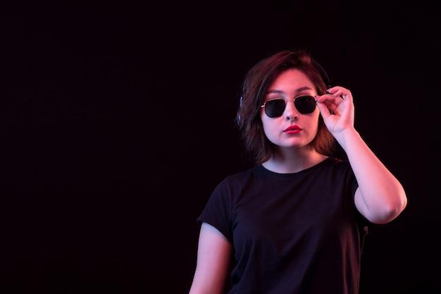 Jovem mulher com óculos escuros e camiseta preta