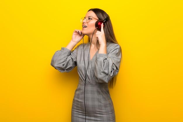 Jovem mulher com óculos na parede amarela, ouvindo música com fones de ouvido