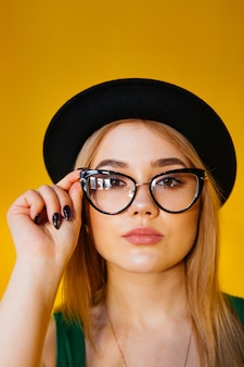 Jovem mulher com óculos no chapéu preto amarelo