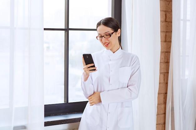 Jovem mulher com óculos no jaleco, segurando mensagens de verificação no celular perto da janela.