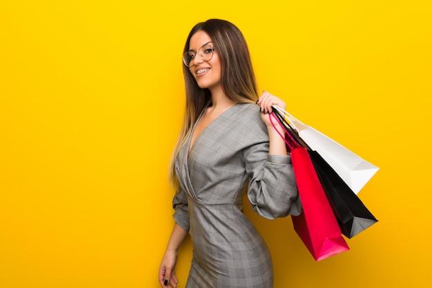 Jovem mulher com óculos parede amarela segurando um monte de sacolas de compras
